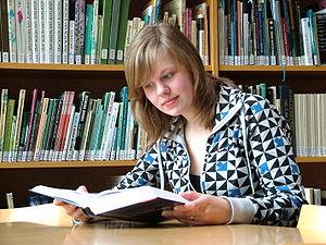 英语:阅读书的一名年轻女子的照片......